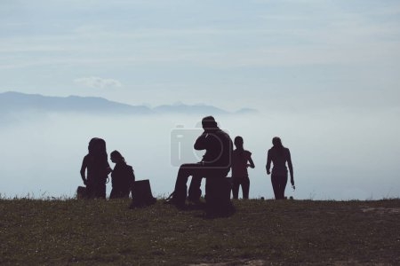 People silhouette on the top of mountain. Tourists enjoying beautiful mountain view.
