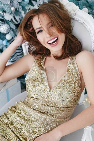 Photo pour Superbe femme brune dans une soirée or robe célébrant le nouvel an et Noël, portrait de beauté souriant modèle fille. - image libre de droit