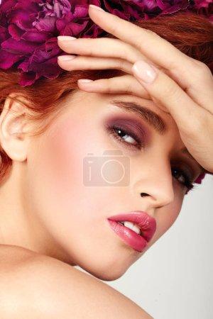 Photo pour Maquillage visage de beauté fashion gingembre fille. Portrait avec des fleurs de pivoine. Femme Sexy glamour avec un maquillage tendance violet parfait, visage contour des lèvres roses. Tendances beauté, vernis à ongles nude, salon - image libre de droit