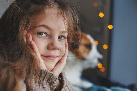 Photo pour Portrait d'une mignonne petite fille souriante avec jack chiot terrier russell derrière. Froide automne ou en hiver, agréable week-end à la maison - image libre de droit