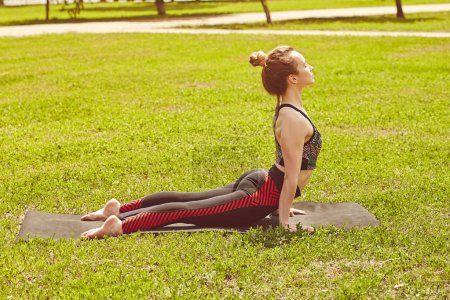 Photo for Woman doing yoga in park on green grass. Flexibility, activity, yoga, pilates, health concept - Royalty Free Image