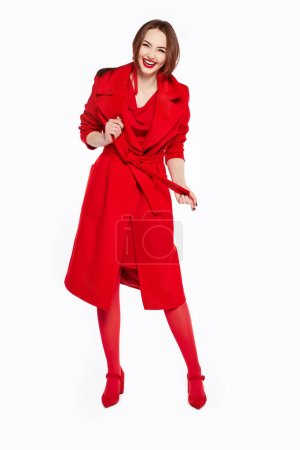 Photo for Happy smiling joyful lady in red coat and pants looking in camera. Sexy brunette young woman. Stylish female fashionable red outfit and hairstyle. Full length - Royalty Free Image