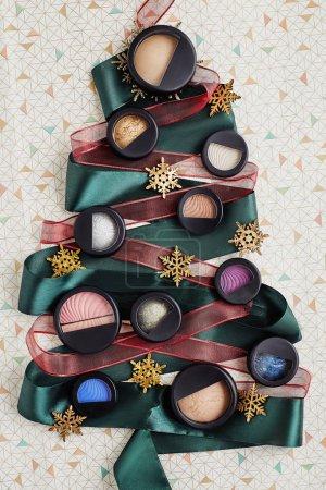 Photo pour Exemples de produits cosmétiques pour appliquent le maquillage sur l'arbre de Noël fabriqués à partir d'un ruban vert. Produits pour le visage parfait peau maquillage. Décoration de Noël et nouvel an - image libre de droit