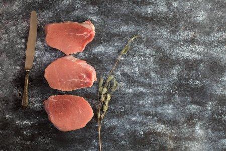 Photo pour Tranches de viande de porc crue. Coupe fraîche de la viande de porc sur un fond en bois sombre. Vue de dessus, espace pour le texte - image libre de droit