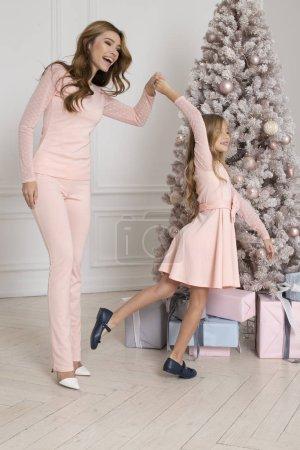 Foto de Mamá e hija celebrando la Navidad, bailando cerca de abeto con presenta. Aspecto familiar. Año nuevo junto - Imagen libre de derechos
