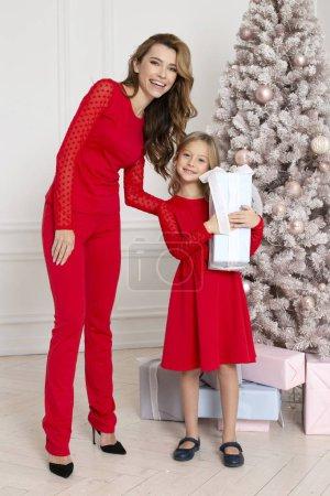 Photo pour La mère donne ses cadeaux de Noël fille debout près de sapin. Air de famille. Nouvel an ensemble. Enfant heureux avec présent - image libre de droit