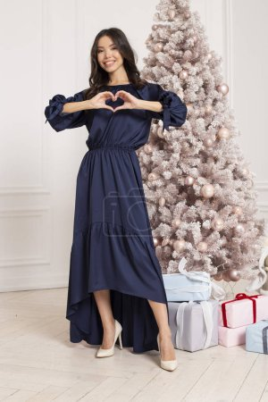 Gorgeous Christmas Winter Fashion Lady in a blue evening dress standing near fir tree showing heart with hands. Beautiful New Year and Christmas decorated background, sale.