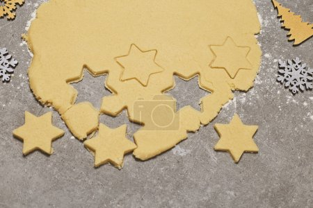 Baking Christmas Gingerbread cookies, gold and silver snowflakes, cinnamon. Stars and fir trees with decoration on grey stone table. Christmas and New year food. Preparing for Christmas, cooking. Top view