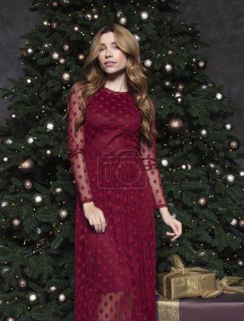 Photo pour Quittés jeune jolie femme en robe rouge en attente près de sapin pour Noël. Concept de vacances et de nouvel an. - image libre de droit