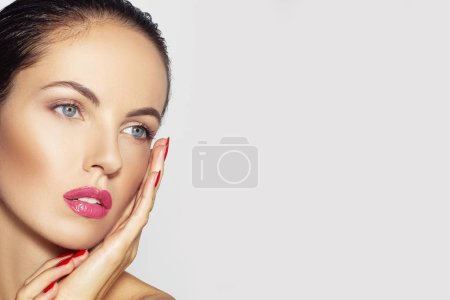 Photo pour Belle jeune belle fille Spa avec maquillage parfait, des lèvres pleines, concept de soins de la peau. Brunette Spa modèle fille sur ongles fond gris, rouge, toucher son visage, horizontale, espace pour le texte - image libre de droit