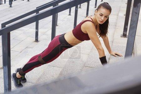 Photo pour Remise en forme sportive femme faisant push-ups en plein air. Belle fille dans les escaliers. Espaces de remise en forme de modèle. Perte de poids. Mode de vie sain. Femelle en bonne santé sportive. - image libre de droit