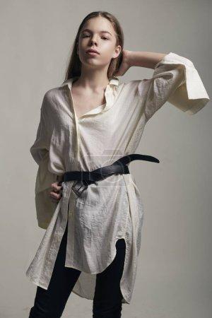 Photo pour Adolescente jeune mannequin posant au studio de vêtements élégants. Style casual, accessoires de beauté, chemise blanche. Arrière-plan de style décontracté, gris haute couture - image libre de droit