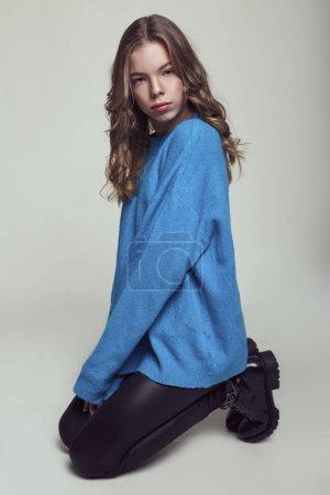 Photo pour Adolescente jeune mannequin posant au studio de vêtements élégants. Style casual, accessoires de beauté, chandail bleu. Arrière-plan de style décontracté, gris haute couture - image libre de droit