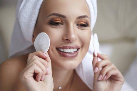 Photo pour Jeune femme souriante belle avec une serviette sur sa tête tenant des tampons de coton dans ses mains. Soins de beauté, spa et soins de la peau. Suppression de maquillage. - image libre de droit