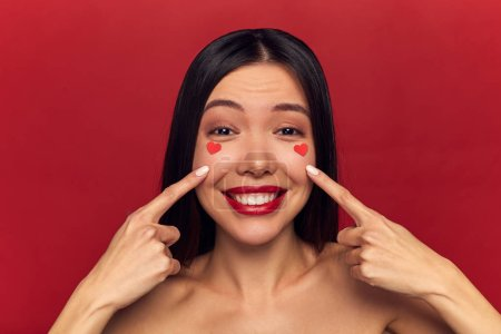 Photo for Beauty portrait of brunette happy smiling woman showing her hearts on face. Valentine's Day portrait of attractive smiling woman isolated on red, studio shot, love make-up - Royalty Free Image