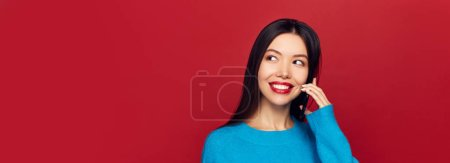 Photo for Portrait of a cute happy girl in blue sweater talking on mobile phone and smiling isolated over red background, copy space - Royalty Free Image