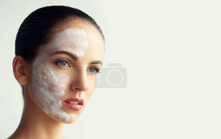 Photo pour Young beautiful spa woman applying facial clay mask cleaning pores. Skin care, spa salon and beauty Treatments - image libre de droit