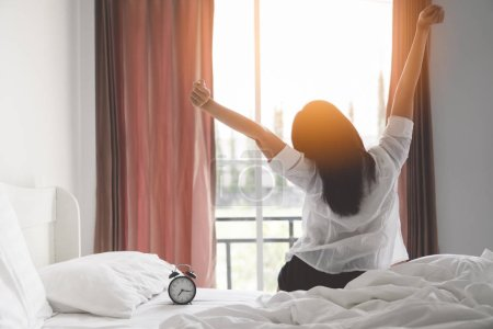 Happy asian woman stretching on bed after waking up at morning in bedroom with sunlight shine through curtains