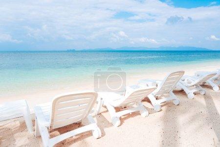 Photo pour Vue latérale des chaises de plage blanche sur la plage tropicale de sable blanc avec un ciel nuageux, fond bleu de la mer calme. Vacances vacances d'été se détendre au soleil sur une chaise longue. Outdoor voyager et prendre le soleil sur les transats. - image libre de droit