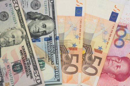 Currencies and money exchange trading concepts from several different country. Pile of various currencies US Dollar bills (USD), Euro and Chinese yuan banknotes for business and finance background.
