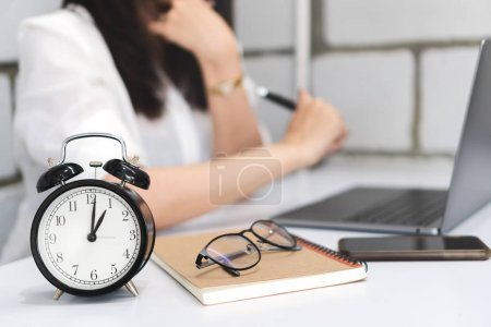 Time management, Close up black alarm clock with blurred background of business woman is working with laptop, smartphone, book, pen and glasses on desk in office. Time to work concept.