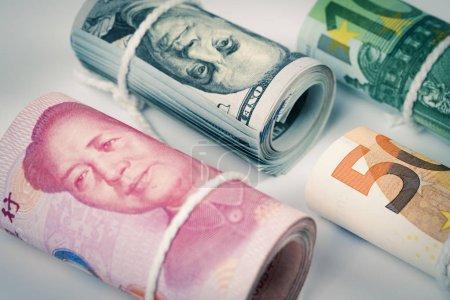Photo pour Devises et concepts de trading de change. Les rouleaux de différentes devises Dollar US, Euro et yuan chinois billets avec bande de corde blanche isolé sur fond blanc . - image libre de droit