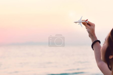 Woman hand holding airplane model in sunset sky and summer sea background dreams of journey in vacation. Travel and air transportation concept. Taking flight and takeoff, Hand with small toy plane.