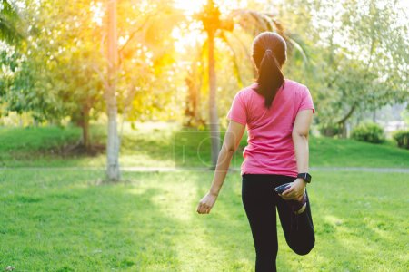 Young fitness woman runner stretching her legs before run and workout in park. Healthy female exercising and warming up outdoor garden in morning in back view. Healthy lifestyle, sport and training.