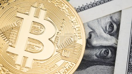 Close up gold bitcoin coins on one hundred US dollar bills background. Cryptocurrency, New digital currency, Bitcoin exchange to money banknotes and accepted payment, Finance and technology concept.
