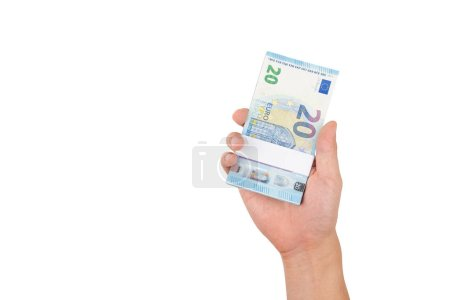 Hand holding stack of twenty euro bills isolated on white background with clipping path. Pile of 20 euro money on hand and giving to you in concept of money exchange, donate, banking and savings.
