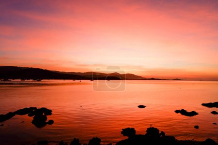 Beautiful blazing sunset landscape at black sea and mountain above orange sky with awesome sun golden reflection on calm sea as a background. Amazing summer sunset view on the beach.