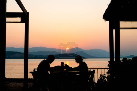 Silhouettes of happy and romantic couple in love sitting together at sunset beach restaurant and looking on menu for dinner. Couple enjoy summer holiday, honeymoon at outdoor dining table in evening.