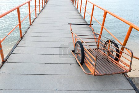 Orange handcart parked on pier walkway with iron railings, Handcart used for carriage of goods to ship.