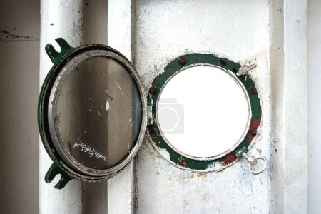 Blank space of vintage circle porthole or window frame at rusted steel side wall on old ferry boat.