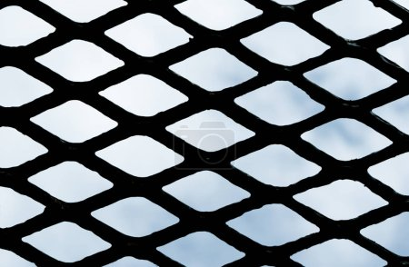 Steel grating texture and background over blue sky.