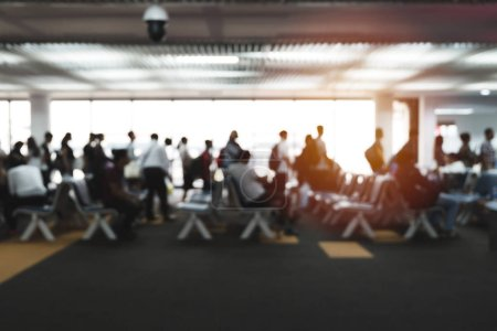 Image floue de défocalisé de file d'attente de voyageurs au terminal arrivée départ à l'aéroport international. Beaucoup de gens assis sur la chaise en zone d'attente de porte, en attente pour le vol à destination