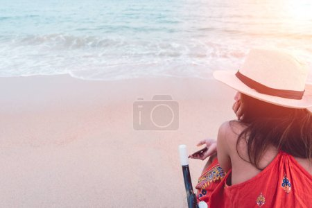 Rear view of young worried woman traveler in hat sitting on beach chair and hand holding smartphone while relaxing on tropical beach and sunset sea background. Summer vacation, travel and relaxation.