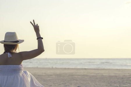 Back side of happy woman sitting on tropical sea and beach showing two fingers or victory sign during sunset. Young woman enjoy life vacation and relaxing in paradise island in vintage tone.