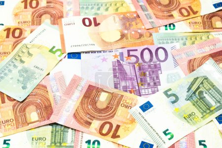 Five hundred euro bill in pile of five and ten euros banknotes background.
