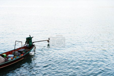 Long tail fishing boat on calm blue sea with sunlight shining on water surface.