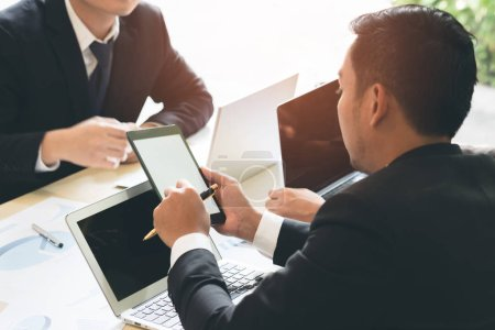 Group of business people meeting and using laptop and touch pad during in conference room. Businessman working hand pointing at screen during discussion and design idea and planning in workplace.