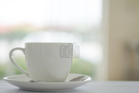 Cup of coffee placed on white table and blurred garden background at coffee shop in fresh morning.