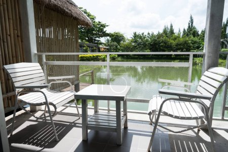 White wooden table and chairs are located on terrace of house and lake view with white steel fence and sun shining in morning. Balcony seating for relaxation.