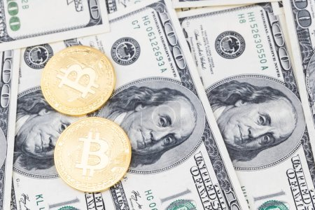 Gold bitcoin coins on one hundred US dollar bills background. Cryptocurrency, New digital currency, Bitcoin exchange to dollar money banknotes and accepted to payment, Finance and technology concept.