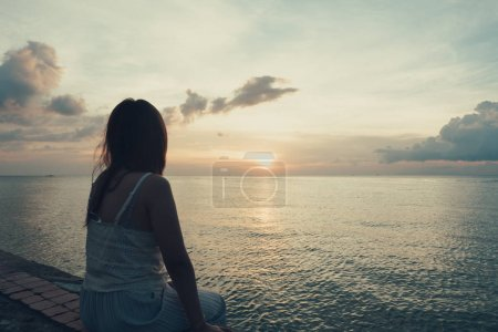 Photo for Silhouette of young woman sitting alone on back side outdoor at tropical island beach missing boyfriend and family in summer sunset. Sad and lonely concept in dark and vintage tone. - Royalty Free Image