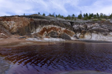lake with red water with dissolved pyrite salts in the desert landscape of a spent quarry