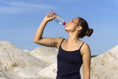 young slender athletic girl drinks water from a plastic bottle after playing sports outdoors