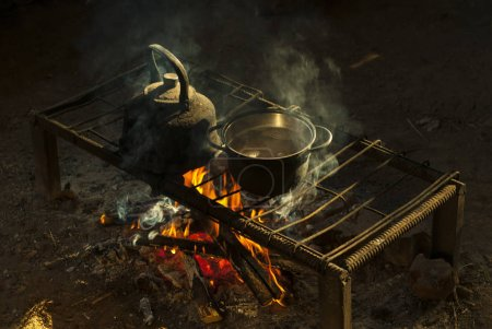 a pot and a kettle stand over a fire on a portable hearth made of metal rods in a nomad's dwelling