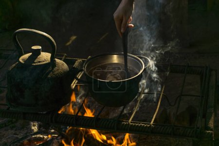 Pot and kettle stand over a fire on a portable hea...