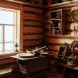 Fragment of the interior of an old peasant log cabin - a table with wooden and ceramic dishes, a kerosene lamp